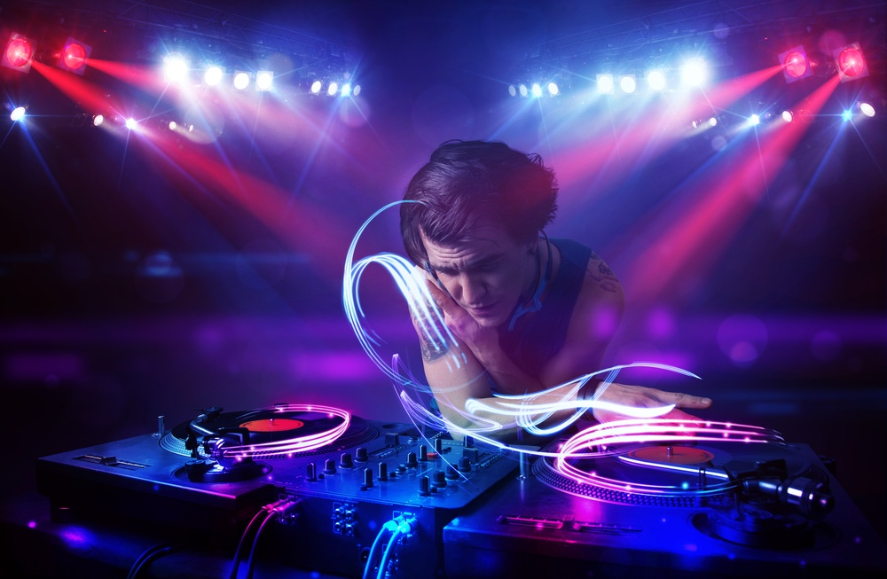 Handsome disc jockey playing music with light beam effects on stage.jpeg