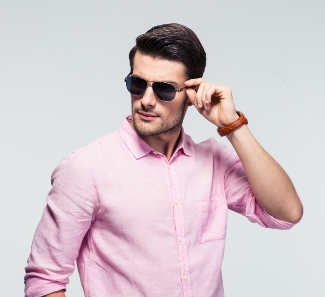 Portrait of a trendy young man in sunglasses and pink shirt over gray background-695924-edited.jpeg